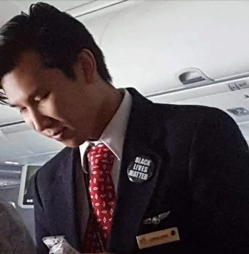 American Airlines flight attendant wearing BLM pin.